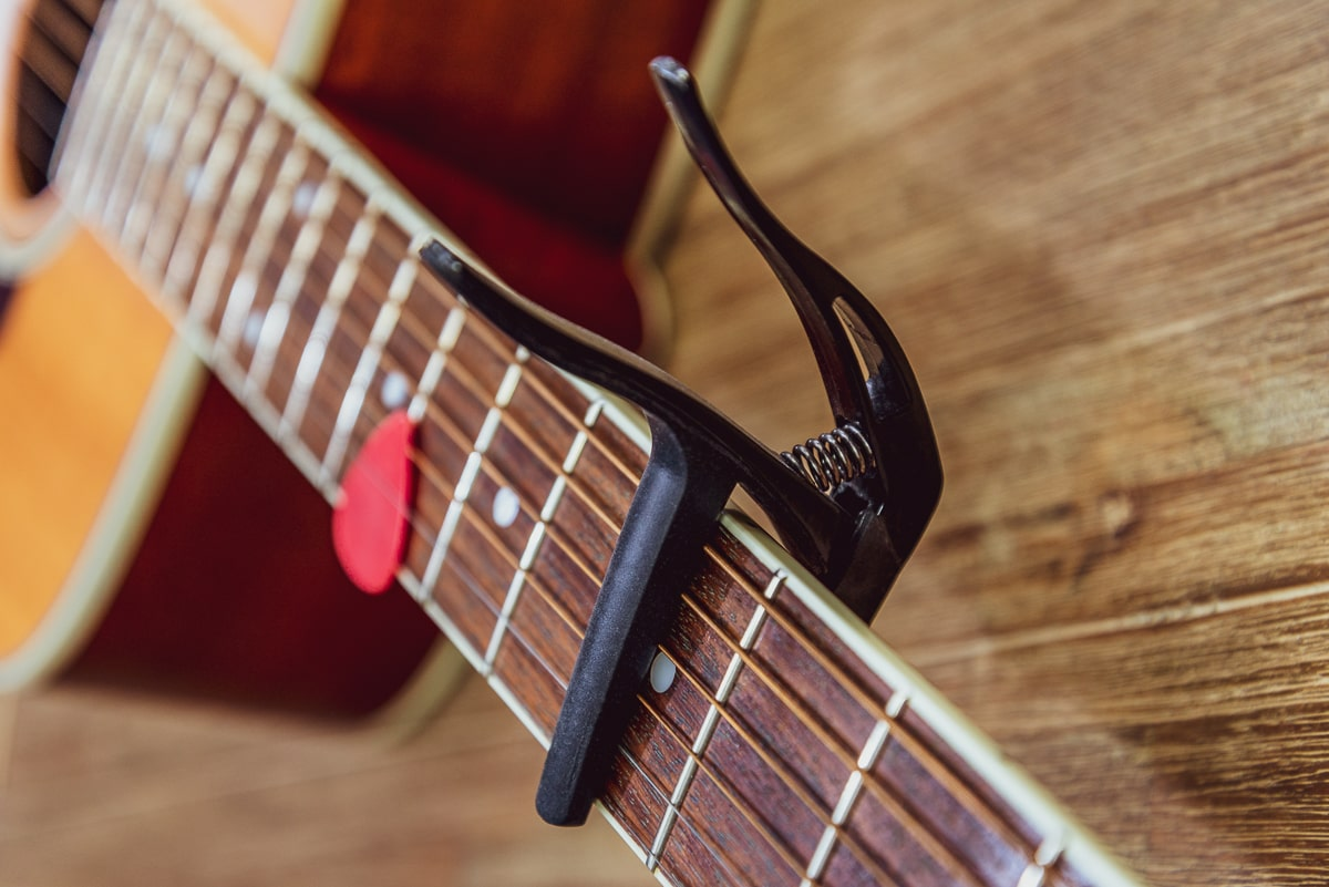 black guitar capo on neck of acoustic guitar with red pick