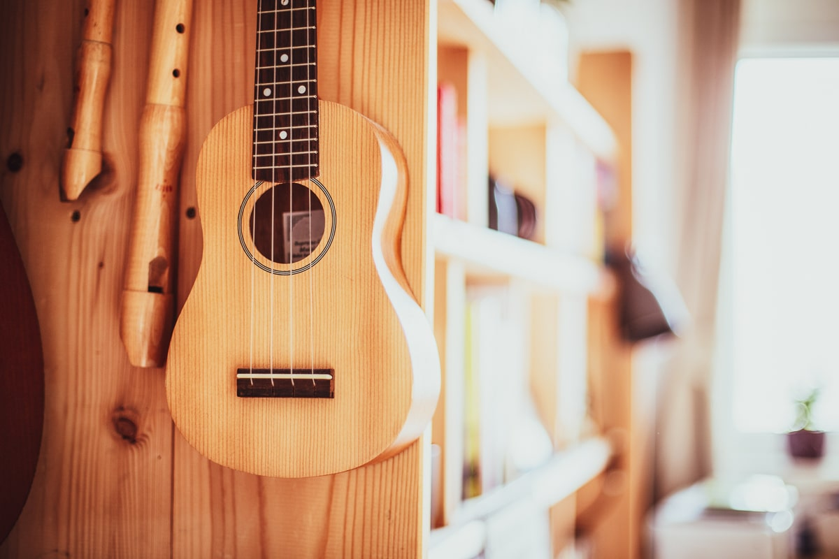 best concert ukulele hanging on side of wooden shelf beside instruments