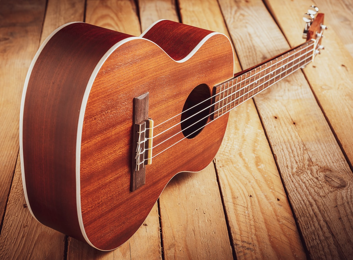 best tenor ukulele with strings on wooden floor