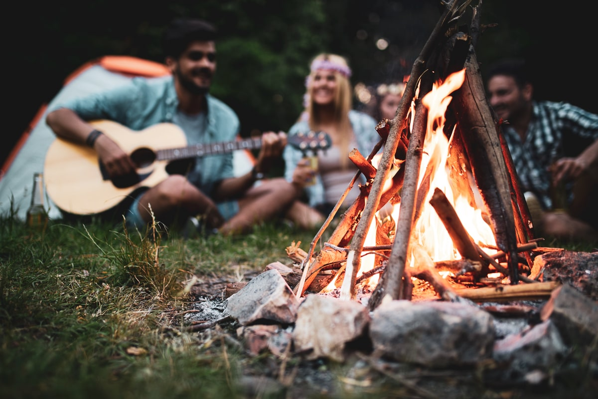 outdoor campfire with people playing guitar campfire songs behind