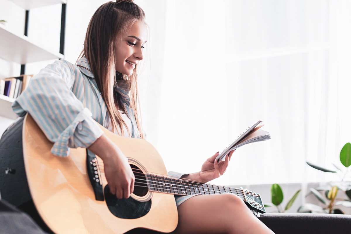 woman reading guitar theory book holding guitar
