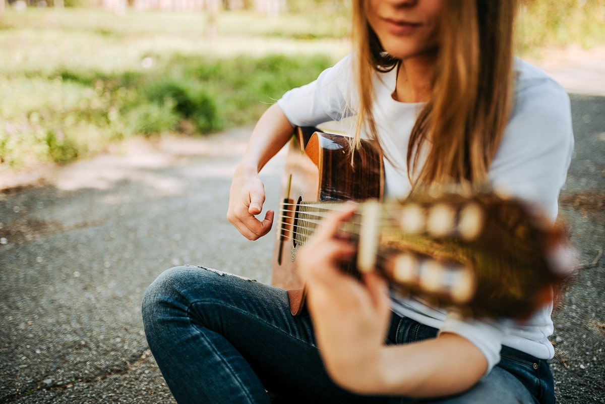 woman sitting with guitar in hands with grass behind