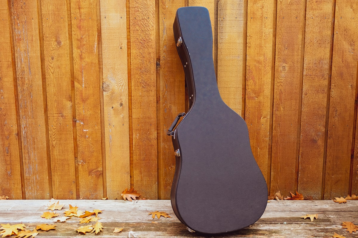 black hard shell acoustic guitar case leaning against wooden wall