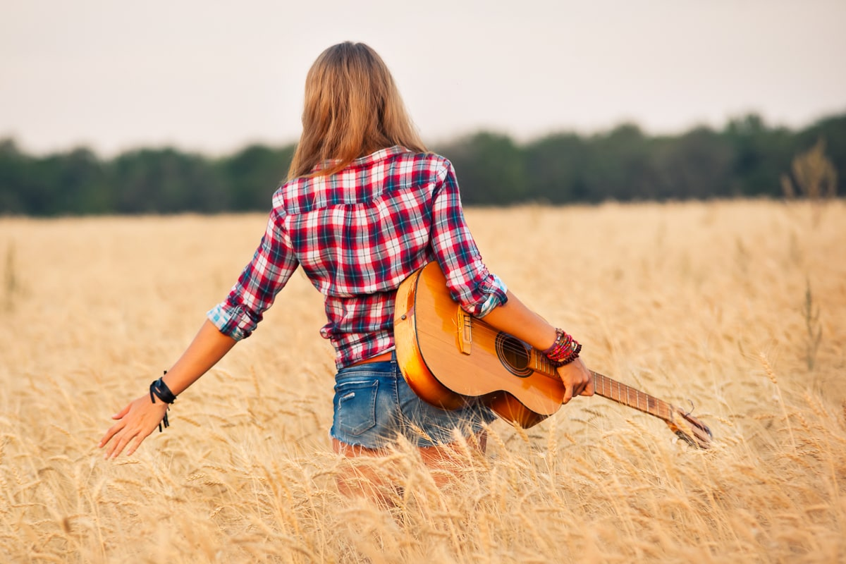 woman with plaid shirt walking in wheat field holding acoustic guitar