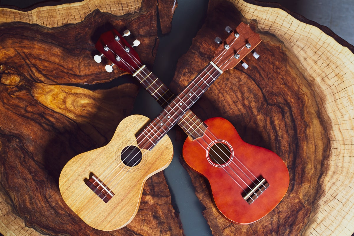 red body ukulele and yellow body different types of ukuleles on wooden table