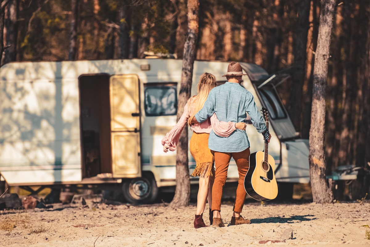 man and women with travel guitar walking toward rv in forest