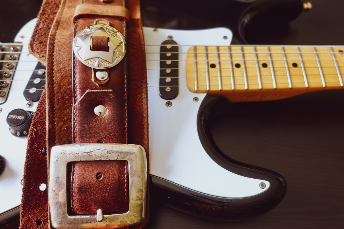 leather guitar strap sitting on electric guitar on table