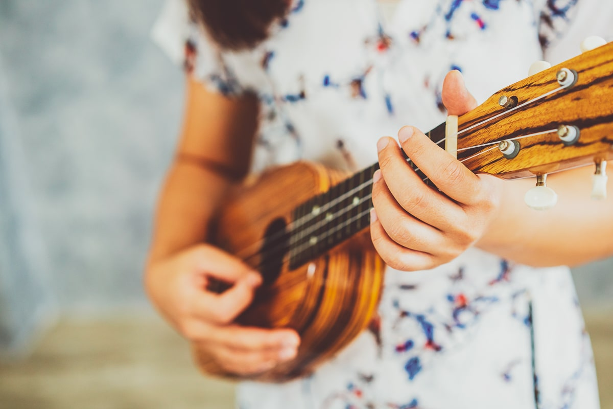 woman in dress holding pineapple ukulele