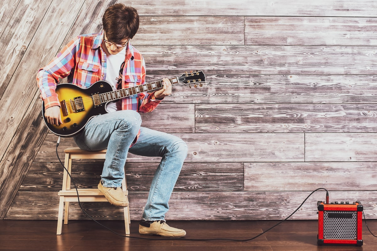 guy sitting in guitar stool playing guitar with amp beside