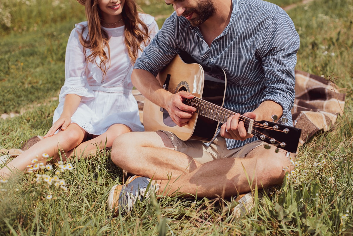 man playing guitar love song sitting beside woman on grass